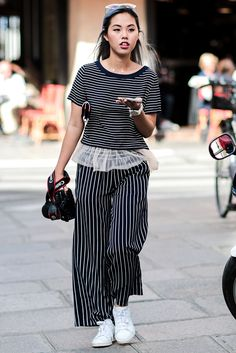 A superlative stripe show by this Paris Fashion Week street-styler. The horizontal bands of her black and white T-shirt are offset by the vertical lines of her wide-leg trousers – and the little peekaboo netted hem is simply adorable