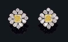 A FINE PAIR OF FANCY INTENSE YELLOW DIAMOND AND DIAMOND EAR CLIPS, BY GRAFF    Each set with a modified rectangular-cut fancy intense yellow diamond weighing 4.07 and 4.14 carats, in a pear-shaped diamond cluster surround with circular-cut diamond cardinal points    Signed Graff, no. 3944