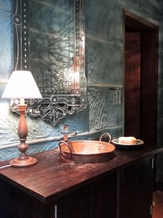 Esse lavabo tem paredes feitas de pau a pique, pintadas na cor petróleo. Um tacho de cobre faz às vezes de cuba e um móvel antigo foi transformado em gabinete | Projeto Paula Gambier Arquitetura de Interiores