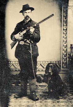 Standing at the ready and accompanied by his rather mournful hound, this huntsman poses with a standard-grade Winchester Model 1873 lever-action, repeating sporting rifle having a case-hardened frame and an adjustable buckhorn rear sight. Two indistinguishable pocket-sized cartridge revolvers are thrust into the fellow's belt in this circa 1880-85 tintype.  – Courtesy Dickinson Research Center, National Cowboy & Western Heritage Museum, 2003.034 –