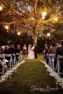 The aisle of the ceremony site will be lined with soft ivory rose petals. Lanterns hanging from tree