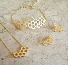 This trio jewelry set features a gold plated beehive necklace, bracelet and earrings. Present this beautiful set to your mother, aunt, sister and your loved ones and have them fall in love♥ Honeycomb Necklace: H o n e y c o m b D i m e n s i o n s : 19 mm x 10 mm M a t e r i a l s : Gold plating over brass C h a i n L e n g t h : 18 inches  Honeycomb Bracelet: H o n e y c o m b D i m e n s i o n s : 1.5mm x 4.5mm M a t e r i a l s : 18k gold plating over stainless steel A d j u s t a b l e…