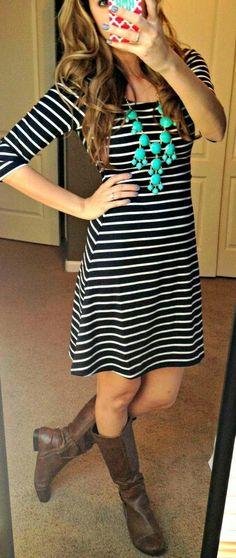 La chica lleva un vestido a rayas que es azul marino y blanco, botas de cuero, y un collar azul.