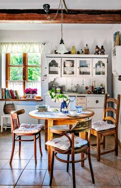STYL WIEJSKI. Lambrekiny i zazdrostki są wystarczającą ozdobą okna. Szczelne zasłony, które izolują od otoczenia, to typowo miejski wynalazek. Każde krzesło z innej bajki, a w tle - malowany na biało kredens. Im większa różnorodność, tym autentyczniejszy wystrój.