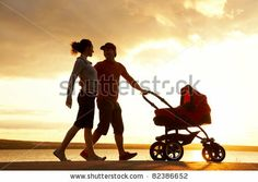 Silhouettes of happy parents walking with stroller on the seacoast - stock photo