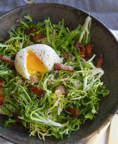Lyonniase Salad made from frissee salad leaves tossed in a warm vinaigrette poached egg and crispy thick-slab bacon pieces