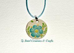 Ceramic pendant  https://www.etsy.com/listing/176320171/ceramic-pendant-with-blue-flower-on-a