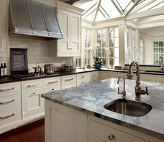 O'Brien Harris: Gorgeous L shaped kitchen with ivory kitchen cabinets paired with  honed blue granite ...