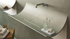 Un lavabo di design, rivestito a mosaico o in resina, che sembra staccarsi dalla parete della stanza da bagno.