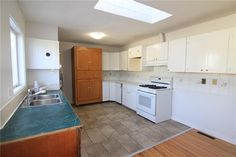 Kitchen features a skylight for extra natural light, lots of cabinets, gas stove, upgraded fridge. Diamond Realty & Associates Ltd. Selling Real Estate, Gas Stove, Skylight, Home Buying, Open House, Natural Light, Cabinets, Diamond, Kitchen