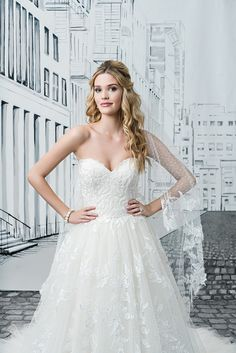 Classic styling with gorgeous lace placement. This ball gown has a sweetheart neckline, natural waist, a full tulle skirt, cathedral length train, and a matching fingertip length veil included.