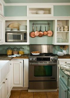 The different colored countertops kind of perplexes me, but I love the blue walls and copper pots n pans