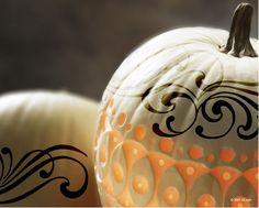 pumpkin carved into art and drilled with holes to make twinkly lights, scroll work around top