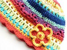 Lustige Häkelmütze für kleine Hippiemädchen in regenbogenbunten Farben, verziert mit einem Blümchen. Suchst du nicht gerade nach so einer Häkelmütze?