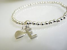 This silver bespoke bracelet is complimented by the initial of your choice along with a heart pendant.