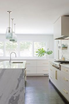 Well appointed light gray contemporary kitchen boasts smoke gray glass light pendants hung above a white marble waterfall island countertop finished with a stainless steel sink and a polished nickel gooseneck faucet.