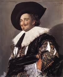 Laughing Cavalier by Frans Hals, 1624 an unstarched falling ruff, a low crowned, wide brimmed Cavalier style hat. Lace cuffs, a soft doublet with vertical slashes in the sleeves. A sash high on the waist that gives the illusion of a shortened torso, Van Dyke beard and moustache.