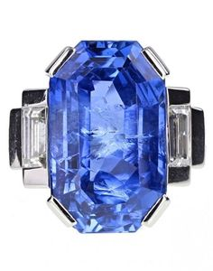 An Art Deco Sapphire and Diamond Ring, by Mauboussin. Featuring an elongated octagonal-cut blue sapphire of approximately 14 carats, mounted in four platinum claws, and flanked on each side by a single baguette-cut diamond on stepped shoulders.