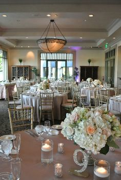The bistro was set with mocha linens, lush peach and white centerpieces, mercury glass voices, and chivalry chairs. Glitter table numbers added glamour and drama.  Las Vegas Wedding PlannerAndrea Eppolito| Las Vegas Venue:Siena Golf Course|Floral & Decor:Naakiti FloralandSit On This