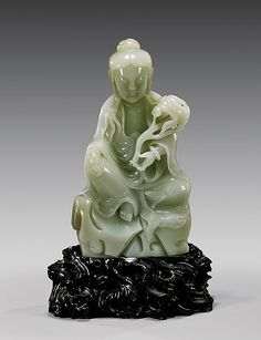 """CHINESE CARVED CELADON JADE GUANYIN 青玉雕觀音坐像 Finely carved and polished, Chinese celadon jade figure; of Guanyin seated in a position of ease upon rockery, holding a ruyi scepter; the jade of fine even coloration with some slight tan suffusions to verso; H: 6 1/2""""; lacquered openwork wood stand"""