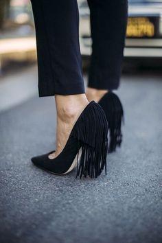 Black suede heels with fringes.