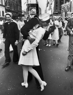 An American sailor passionately kisses a nurse as thousands jam into Times Square to celebrate the long-awaited victory over Japan in World War II.