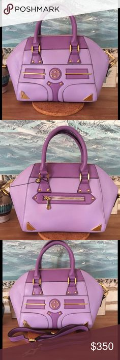 """NWOT Leather Segolene Noir Violet/Gold Satchel SNOIR102VIOLET Segolene Noir convertible leather satchel/shoulder bag is absolutely stunning with gorgeous detail. Light lilac w/dark lilac accents & gold hardware. Plastic still on some hardware. Interior lining with Noir logo, has one zipper & two slip pockets. Lots of room for your necessities. Includes separate drop tag, attached key fob,and detachable shoulder strap with decorative clips. Metal feet. 15""""W x 9""""H x 4""""D.  3.5"""" drop - carry…"""