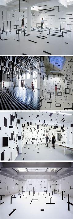 Minimalisme et noir et blanc    L'artiste italien, Esther Stocker, n'en est pas à son coup d'essai dans ces installations et peintures murales exclusivement en noir et blanc. Depuis plusieurs années déjà, il investie toute sorte de lieux et les habillent du sol au plafond de ses éléments graphiques en 2D et 3D très géométriques.