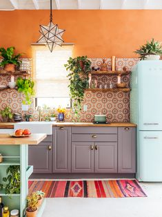 Colorful Kitchens: Cheerful boho-eclectic kitchen with terracotta orange walls and mint blue SMEG refrigerator | NONAGON.style