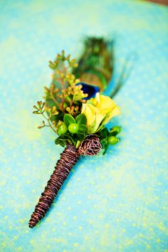 Such a fun boutonniere with a peacock feather and yellow flowers wrapped in wire by Morrison Floral. Photo by Tara