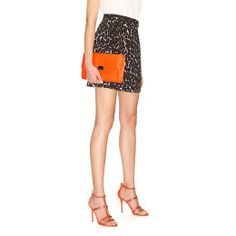 The Jimmy Choo Reese clutch and thistle sandal in Neon Flame