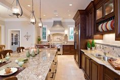 """To create a relaxing and inviting kitchen for entertaining friends, the homeowner wanted a muted color palette and """"soft"""" materials. The large island seats four comfortably and also stores seldom-used holiday dishware and serving pieces. Note the seamless single slab of granite serving as the island counter."""