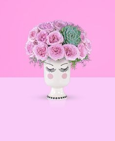 "There's nothing more disarming than an elegant woman with a sparkling wit. This whimsical bouquet pairs our vintage-inspired vase with a coiffure of fragrant, feminine Pink O'Hara Garden Roses. Wisps of Asparagus Fern soften the lines between arrangement and vase, and the ""Tippy"" Succulent adds a playful focal point. It's an arrangement that can't help but delight those stylish and always-up-for-some-fun ladies in your life."