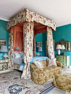 """In Lorry Newhouse's <a href=""""http://www.architecturaldigest.com/story/lorry-newhouse-rose-cumming-new-york-park-avenue-duplex-article"""">Manhattan duplex</a> by Rain Phillips, a canopy made from a Lee Jofa print adds Anglo-country glamour to the master suite, which is painted in a Benjamin Moore blue. The sofa and ottoman are clad in an arabesque wool, the fringed Fortuny-fabric pillows are from David Duncan Antiques, and the carpet is vintage."""