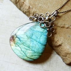 Labradorite pendant. Stunning piece. With the grid behind it, it almost looks like a fragment of a map.