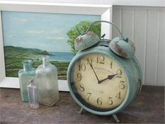 Antique Blue Vintage Style Metal Clock with French cafe graphic. Inspired by old clocks found throughout Paris Flea Markets, this large Antique Blue Vintage Style Metal Clock will brighten your farmhouse decor. The antique French country blue finish has a rustic patina for added charm. The big, bold numbers make it easy to read.