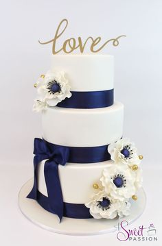 Love Anemone Engagement/Wedding Cake - covered in white with navy satin ribbon and gold embellishments!  www.asweetpassion.com