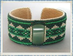 Jade ImmortalGreen Jade Loom Beaded Cuff by ElementalNature, $60.00 The focal is a lovely piece of polished new jade in a light green color. The loomed strip is done in two shades of green and silver in a diamond pattern. The strip is stitched to tan microsuede. I bead embroidered around the strip. The piece is finished with an aluminum bracelet blank and lined with tan microsuede.