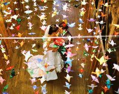 Girlanden aus bunten Origami Vögeln drapieren