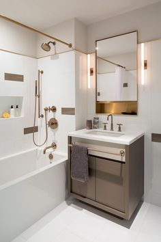 Gorgeous bathroom features taupe veneer vanity with built-in towel bar topped with white quartz framing single bowl sink paired with brass gooseneck faucet under gold vanity mirror flanked by slim wand light sconces.