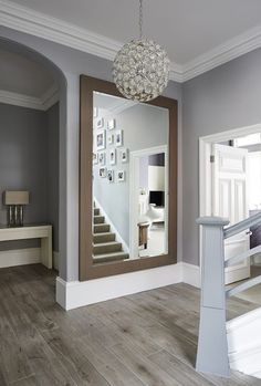 Mirror bottom of stairs? This is contemporary design at its finest, transforming a traditional space into modern living, creating an ambiance of welcome and warmth.