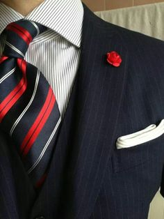 Navy pinstripe suit, white shirt with light grey dress stripes, navy tie with red & white stripes