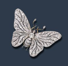 AN ATTRACTIVE BUTTERFLY BROOCH   Centering upon an old European-cut diamond body, enhanced by cabochon sapphire eyes, extending pierced old European-cut diamond wings and polished gold antennae set with old European-cut diamond terminals, mounted in platinum and gold