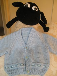 Baby Boy's Blue V-neck cardigan with ribbon detail – 0 – 3 months  This cute little blue cardigan, with 3 cartoon buttons, is suitable for a child aged 0-3 months.  It is trimmed with blue satin ribbon, securely stitched in place so it won't come loose as the cardigan stretches with the growth of your child.