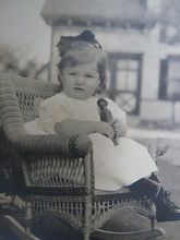 Precious little girl (Edith) sitting in wicker chair holding a carved doll. Early 20th century?