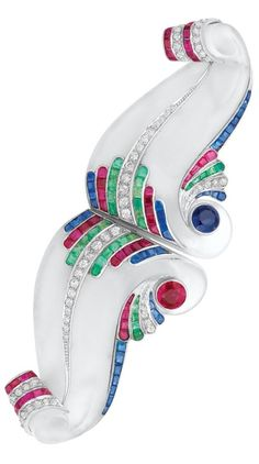 An Art Deco Frosted Rock Crystal, Coloured Stone and Diamond Double Clip-Brooch, Circa 1935. Platinum, 14 kt. white gold, the bold frosted rock crystal clips carved in a stylised scroll motif centring one round collet-set sapphire and one round ruby, acccented by tapered curved ribbons of small old-mine cut diamonds, rectangular-cut sapphires and rubies, signed R&F, with hallmarks.