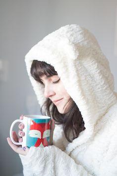 Foto com clima aconchegante de outono/inverno. Mulher com roupão branco/creme fofinho e aconchegante (com orelhinhas de urso) segurando uma caneca com desenho de raposa e chá dentro.  Post inspirador compartilhando pequenas felicidades do dia-a-dia.