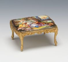 """A Swiss Miniature Enamel Table Music Box  139. A Swiss Miniature Enamel Table Music Box  2 x 4 x 3 in.  Fancy gilt metal table with enameled romantic pastoral scene inset in the top, winding key for music box marked """"Swiss Made"""". Plays a piece by Mozart. Estimate: 400/600 Sold with Premium:$425 Closed: Jun 19, 2014"""