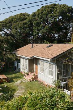 200坪近い敷地には樹木もいっぱい。外観はアメリカ東海岸のケープコッドスタイルで、外壁の羽目板と切妻屋根が特徴。外壁に塗った淡いグレーのペンキは、アメリカで調合してもらったもの。 Cute House, My House, Building Design, Building A House, Greenhouse Cafe, Navy Houses, House Landscape, Cabins And Cottages, Space Architecture