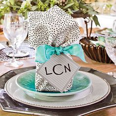 Create a Double-Duty Place Card | Use a whimsical print napkin and a colorful ribbon to camouflage party favors. Attach handwritten gift tags, inscribed with each guest's monogram, to arrange seating